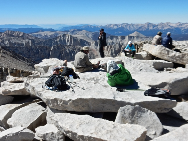 Hikers lounging about on the top of the world.